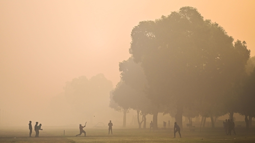 People play cricket at a park amid smoggy conditions in New Delhi, India