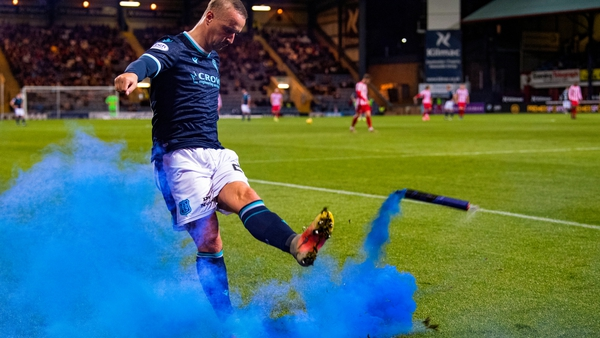 Dundee's Leigh Griffiths kicks a blue smoke bomb thrown on to the pitch by St Johnstone fans