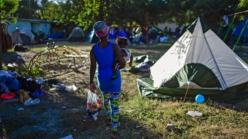 A Haitian woman carrying a toddler walks amid tents before leaving a makeshift camp