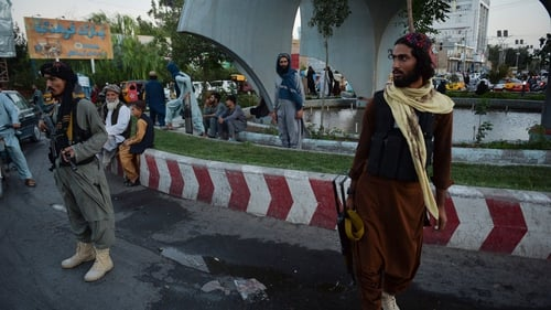Taliban fighters stand guard along a road in Herat (File pic)