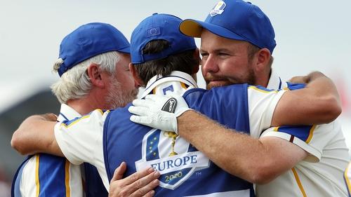 Shane Lowry (R) embraces Bo Martin and Harry Diamond
