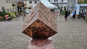 The sculpture is titled 'Meitheal'