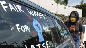 Crystal Kan, a storyboard artist, draws pro-labour signs on cars of union members during a rally at the Motion Picture Editors Guild IATSE Local 700 on September 26 in Los Angeles, CA (Myung J. Chun / Los Angeles Times via Getty Images)