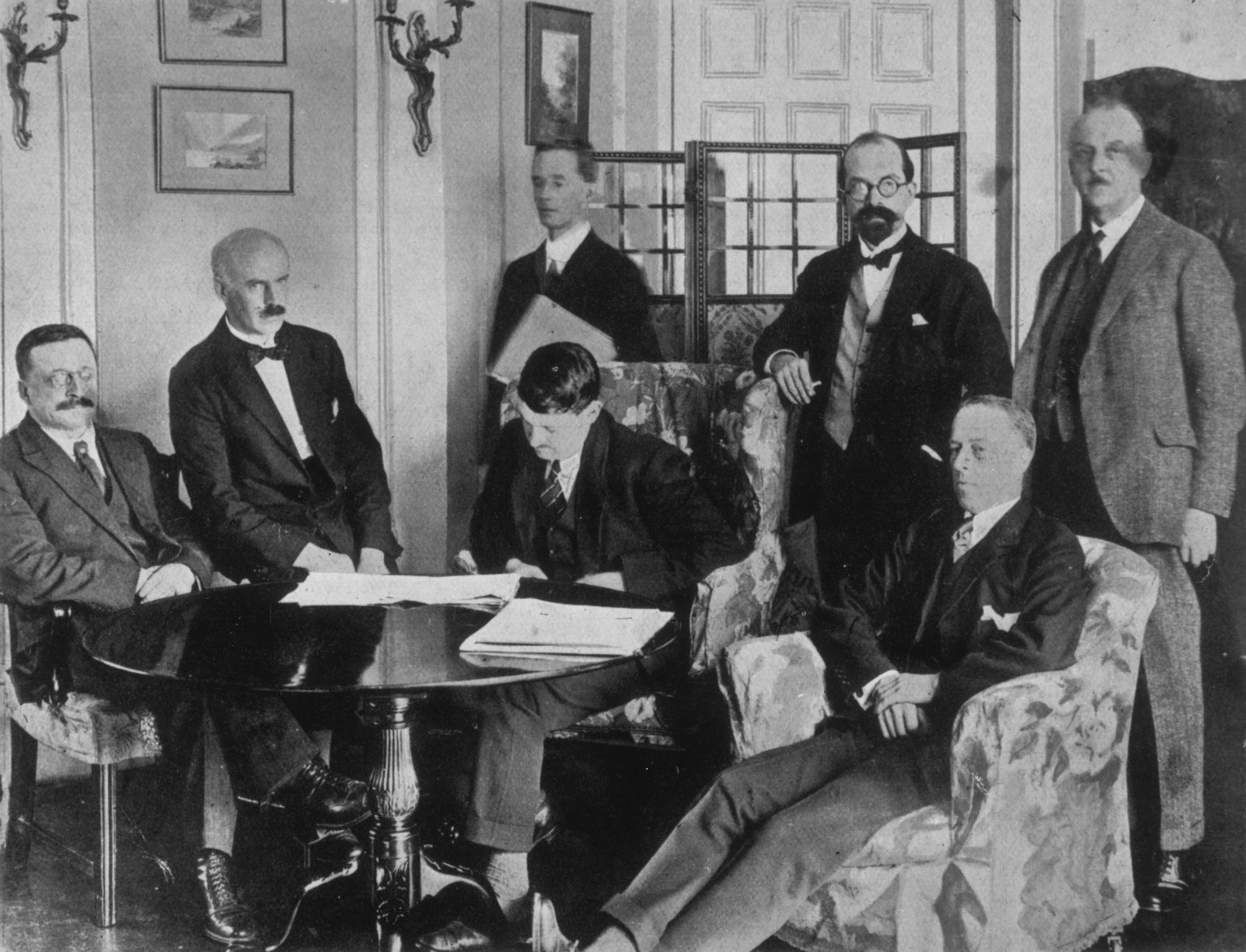 Image - This photo is claimed to capture the moment the Irish delegates began signing the treaty (Credit: Getty Images)