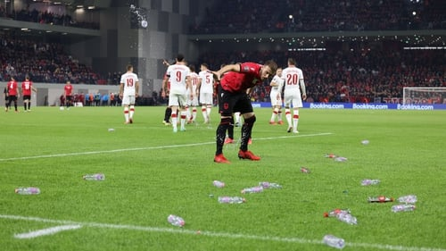 The match is suspended because of fans throwing objects onto the pitch
