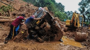 Rescue workers push a overturned vehicle stuck in the mud and debris at a site of a landslide