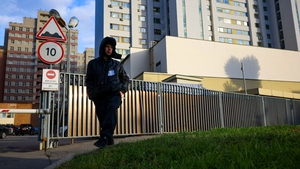 A security guard patrols outside a building that houses the NATO information office in Moscow today