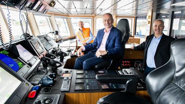 Taoiseach Micheál Martin joins John Wallace (R) Green Rebel CEO and Chris Franks (L) Senior Master of the Roman Rebel vessel