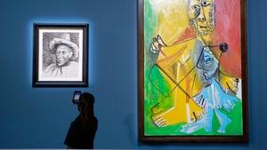 """A guest takes a photograph of Picasso's """"Pierrot,"""" (L) near """"Homme et enfant"""""""