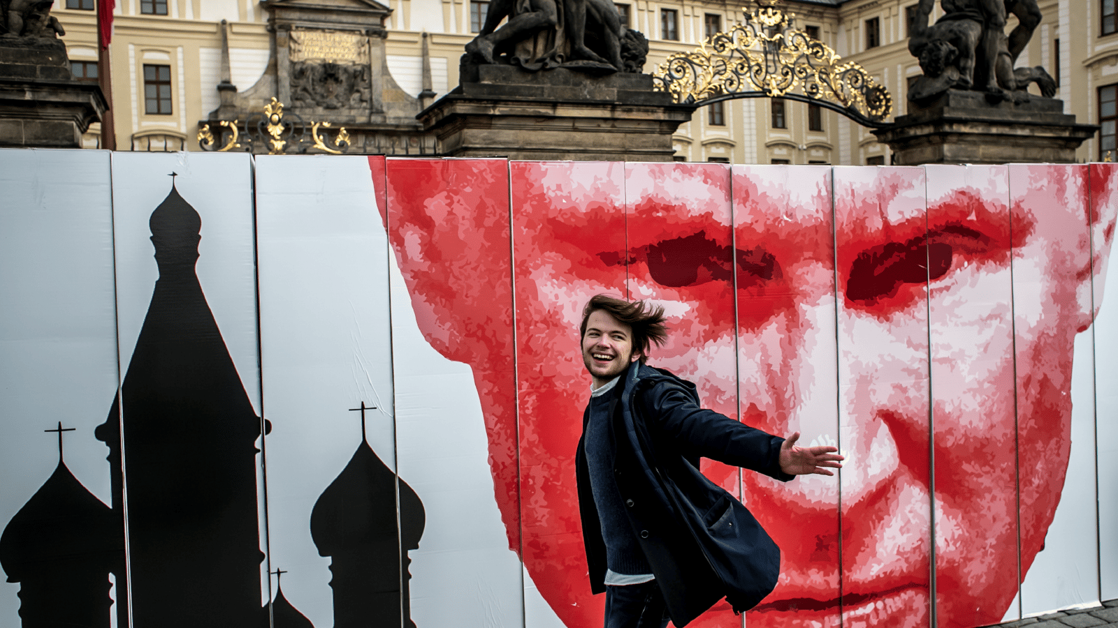Image - A man passes a symbolic wall during a protest in front of the Prague Castle.